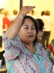 Elvira Ortega motions throwing a bowling  ball during a video game of Kinect Bowling at San Juan Senior Center.