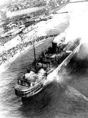 After the disaster, the S.S. Morro Castle, abandoned, adrift and still burning, ran aground on the beach in Asbury Park. For a time, the wreck became a major tourist attraction with ordinary people driving to the city from all over the Tri-State area to pose for macabre photos in front of the ship. This aerial photo was taken by an Associated Press photographer on Sept. 9, 1934. Note the crowds of local residents and tourists gathered on the beach and Boardwalk.