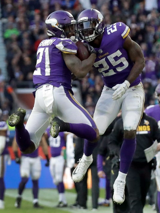 Minnesota Vikings running back Jerick McKinnon (21) is congratulated by teammate Latavius Murray after scoring on a 2-point conversion during the second half of an NFL football game against Cleveland Browns at Twickenham Stadium in London, Sunday Oct. 29, 2017. The Vikings won 33-16. (AP Photo/Matt Dunham)