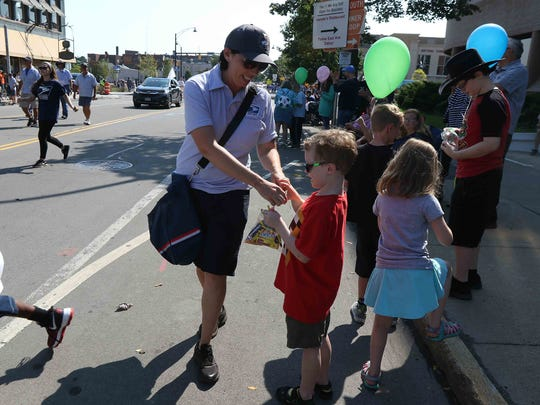 Nancy Klein, with National Association of Letter Carriers Branch 210, gives out candy to people along the parade route.