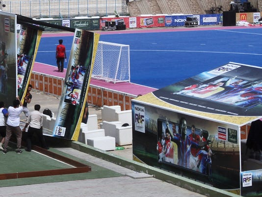 Pakistani workers install advertising boards featuring Ronaldinho, Ryan Gigs and other soccer stars at a stadium ahead of exhibition soccer match in Karachi, Pakistan, Saturday, July 8, 2017. Ronaldinho and Ryan Giggs were among soccer stars to arrive in Pakistan on Saturday to play exhibition matches which organizers hope will boost the sport in the country. (AP Photo/Fareed Khan)