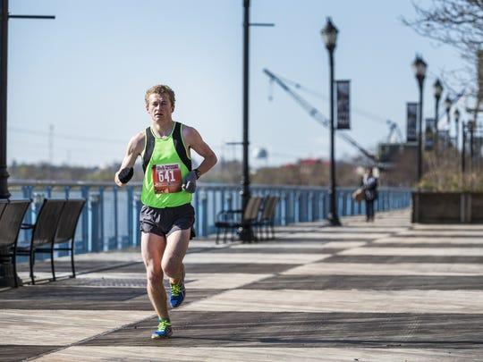 Men's overall winner Nate Alter runs along the riverfront walk in the Caesar Rodney Half-Marathon on Sunday morning.