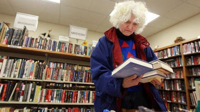 Sandy Kasprzyk, of Florence, looks over books at the Friends of the Campbell County Library's used book sale at the Newport branch in November.