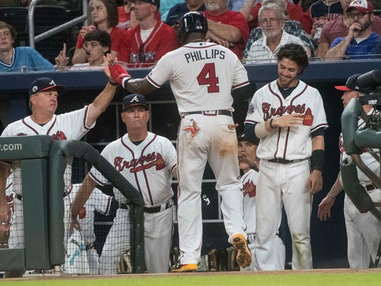 Atlanta Braves' Brandon Phillips (4) is congratulated by hitting coach Kevin Seitzer, left, as he enters the dugout after scoring on a Freddie Freeman single line drive to center field during the seventh inning of a baseball game, Tuesday, Aug. 22, 2017, in Atlanta. The Braves won 4-0. (AP Photo/John Amis)