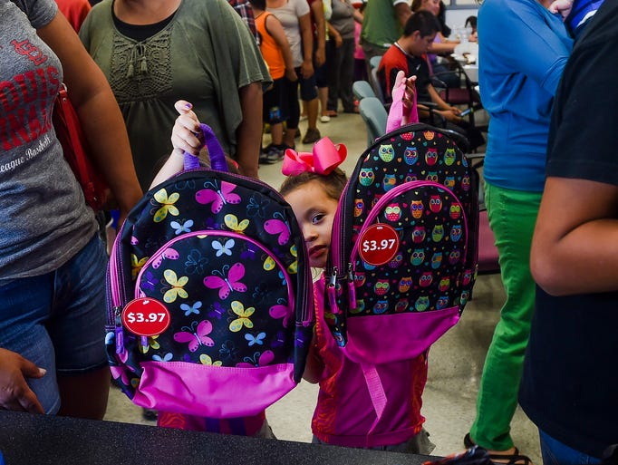 Twins Madeline and Madison Rodriguez hold up their backpacks at the Buckingham and Alta Vista school supplies giveaway during the annual Neighborhood Night Out Tuesday, August 5, 2014. While the event was able to provide school supplies for dozens of children in the area, demand exceeded supplies available. To donate, call Betty Aragon-Mitotes at Museo de las Tres Colonias. (970)412-4536.