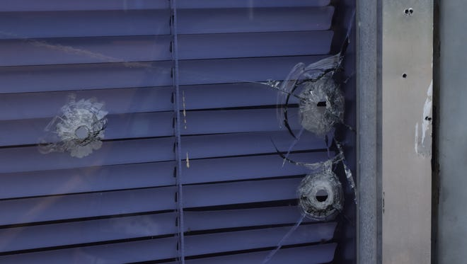 Bullet holes are visible in a window at the United Educational Missionary Baptist Association headquarters off Lee Street in Alexandria, symptomatic of what neighborhood residents say are problems with loitering and crime in the area.