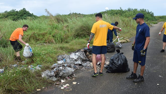 Navy volunteers collect trash on the road next to Eagles Field in Mangilao on Feb. 3, 2017.