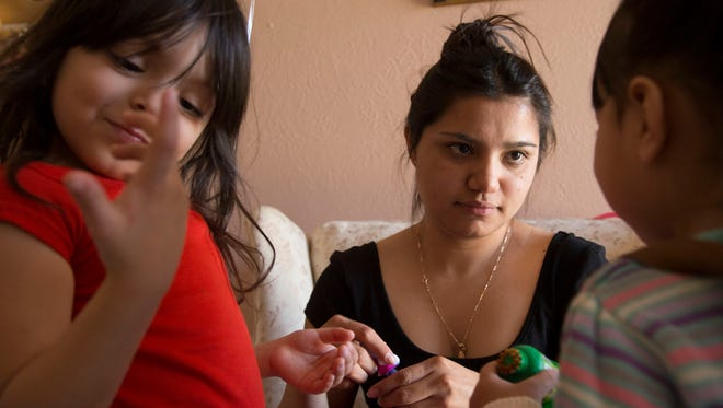 """Noemi Romero, 22, realizes she broke the law when she used her mother's Social Security number to get a job to earn the $465 to apply for the president's deferred-action program, but says, """"I felt like that was the only way."""" After being convicted of a felony related to a workplace raid, she is unable to apply for the program. She now baby-sits her nieces Adeyanne, 4 (left), and Adamaris Romero, 2."""