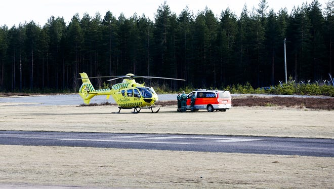 A helicopter and an ambulance are seen at the Jamijarvi Airfield, southwest Finland, on April 20. A small passenger plane carrying parachuters fell to the ground near the airfield on Sunday afternoon.