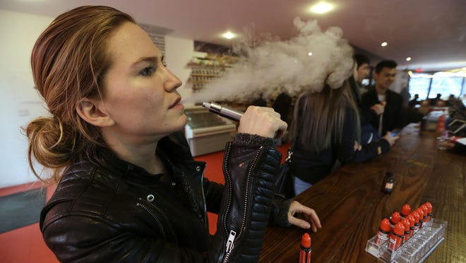 FILE - In this Feb. 20, 2014 photo, Talia Eisenberg, co-founder of the Henley Vaporium, uses her vaping device in New York. City. (AP Photo/Frank Franklin II, File)