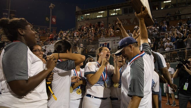 Santa Gertrudis's head coach Thomas De Los Santos holds up the 3A state championship trophy after defeating Hughes Springs at McCombs Field in Austin on Thursday, May 31, 2018.
