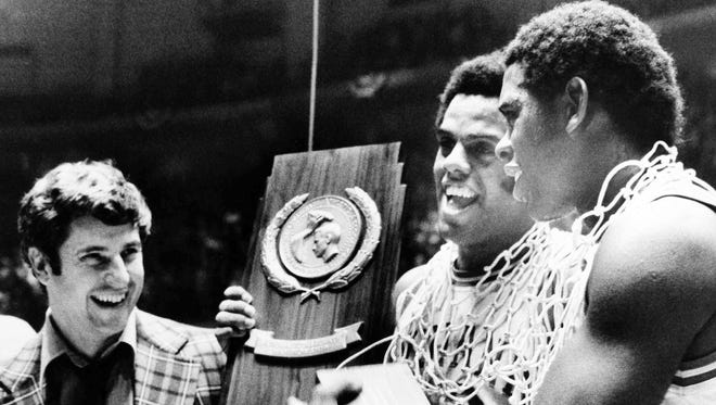 Indiana University coach Bobby Knight, left and players Scott May, center, and Quinn Buckner, right, hold the trophy after winning the NCAA Basketball Championship in Philadelphia on Monday, March 29, 1976. (AP Photo)