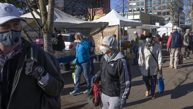 Shoppers wearing masks make their way through a market in downtown Eugene March 21.