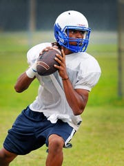 Titusville High School QB Yusuf DeReese runs some plays during Wednesday afternoon's practice .