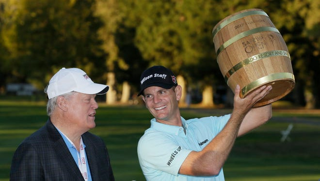 Brendan Steele holds up his trophy on the 18th green of the Silverado Resort North Course after winning the Safeway Open PGA golf tournament Sunday, Oct. 8, 2017, in Napa, Calif. Looking on at left is Hall of Famer Johnny Miller. (AP Photo/Eric Risberg) ORG XMIT: OTK