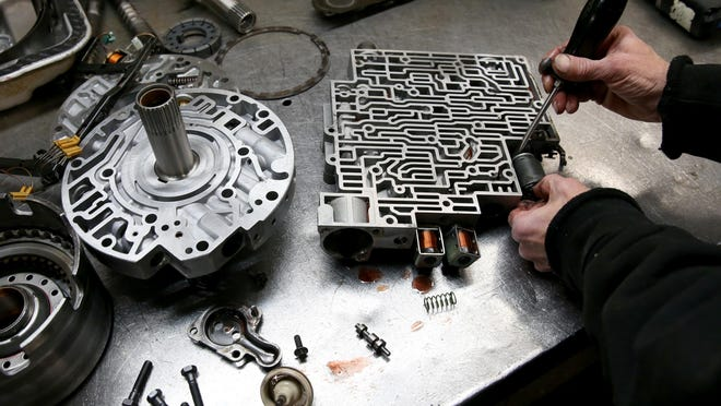 Phil Rock, a transmission technician, at Milt & Ron's Transmission, removes a pressure solenoid off a transmission.