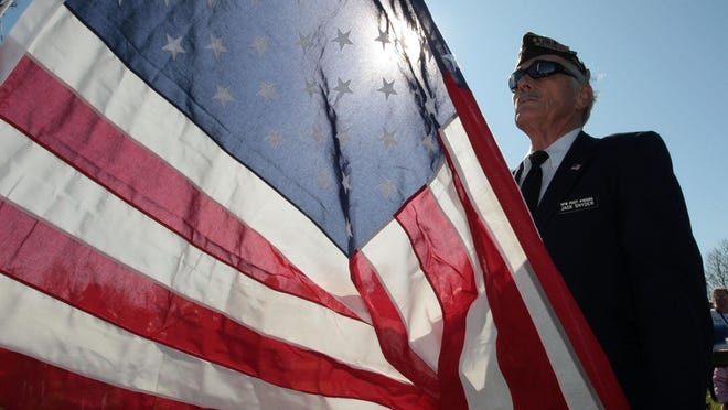 Veteran standing with flag at Veterans Day ceremony.