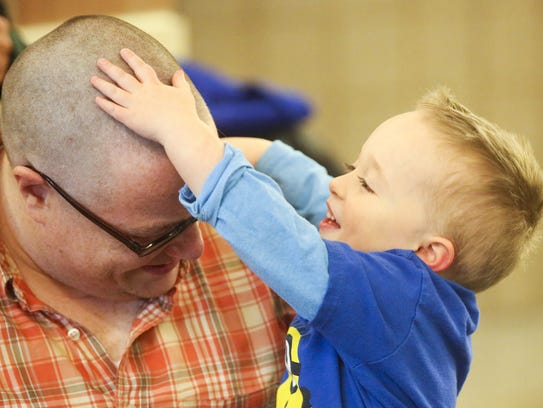 Teddy Makin, 5, rubs on his father's clean shaven head,