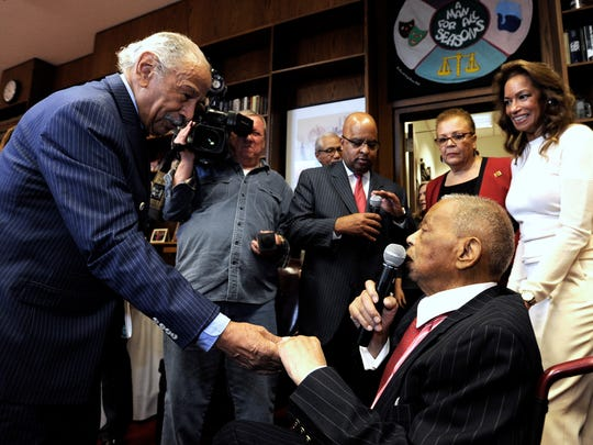 Retired U.S. Congressman John Conyers, left, shakes hands with Judge Damon Keith as the judge introduces VIPs at his 31st Annual Soul Food Luncheon in his offices on Feb. 14, 2018.
