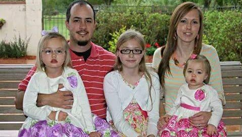 Adam and Sarah McCoy hold their daughters (from left) Emmalin, Layla and Allie McCoy. The family lives in Ball.