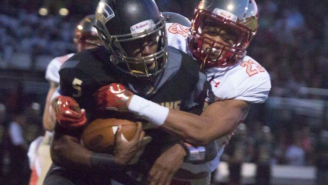 Bergen Catholic's 23 Shayne Butler takes down Paramus Catholic's quarterback Shelton Applewhite during the Bergen Catholic at Paramus Catholic game.