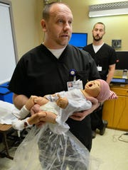 Media/Simulation Specialist Jim Kiess holds an infant mannequin Dec. 17 at St. Cloud Hospital's simulation lab as Simulation Technologist Adam Schulz looks on. It is one of several advanced mannequins used in the lab to train CentraCare Health employees in dealing with a host of medical situations.