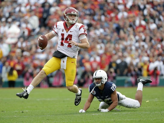 FILE - In this Jan. 2, 2017, file photo, USC quarterback Sam Darnold (14) avoids a sack by Penn State Nittany Lions cornerback John Reid (29) during the first half of the Rose Bowl NCAA college football game in Pasadena, Calif. Darnold is expected to be a first round pick in the NFL Draft. (AP Photo/Doug Benc, File)