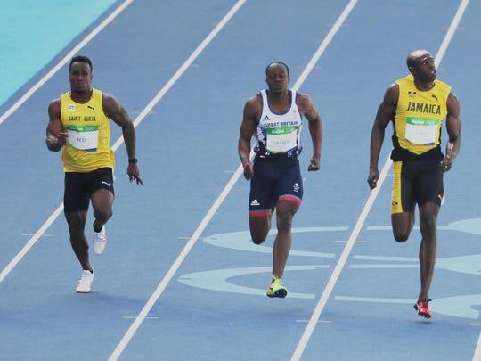 St. Lucia's Jahvid Best, left, runs against Britain's James Dasaolu and Jamaica's Usain Bolt.