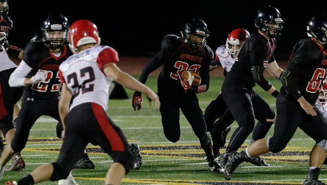 Lourdes Academy's Colyar Newton runs the ball up the middle during the first half Friday against Cambria-Friesland.
