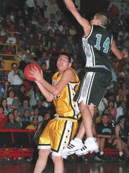 Heart Butte's Mike Chavez, left, looks to shoot under