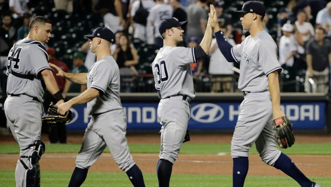 New York Yankees' Aaron Judge, right, celebrates with teammates David Robertson (30), Brett Gardner (11) and catcher Gary Sanchez after a Subway Series game against the Mets Wednesday, Aug. 16, 2017, in New York. The Yankees won 5-3.