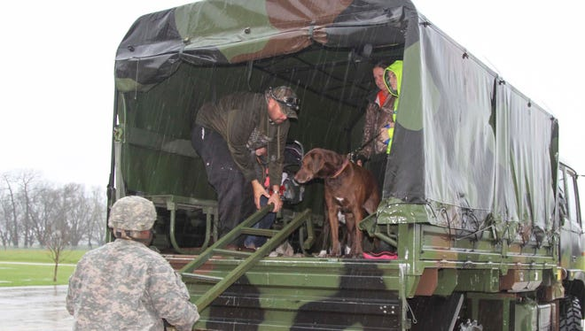 Louisiana National Guardsmen from the 2-108th Cavalry Regiment in Shreveport, La., drop off evacuees at a collection point set up at Parkway High School in Bossier City, during flood response operations, March 9, 2016.