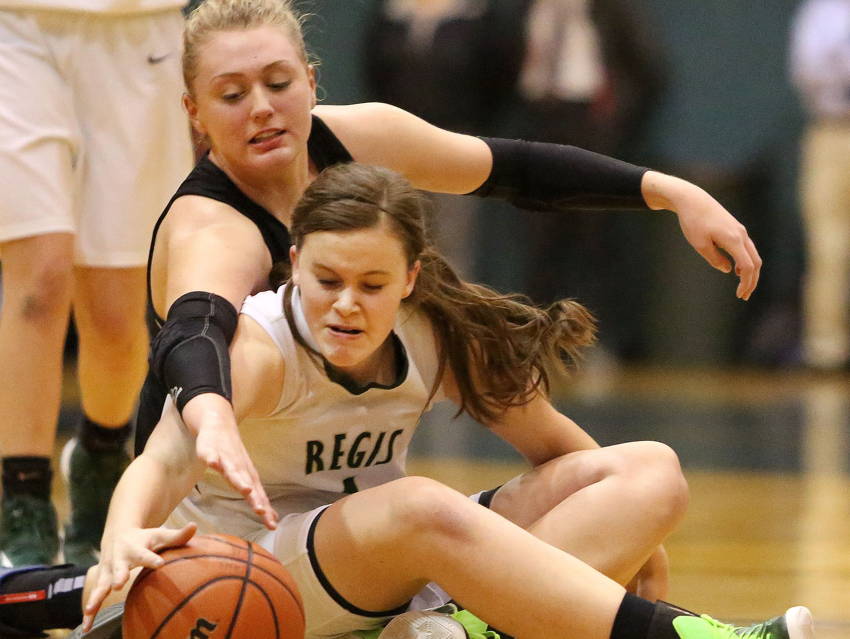Regis High School's Karen Miller, foreground, battles for the ball with Western Mennonite's Emma Gibb during their game on Tuesday.