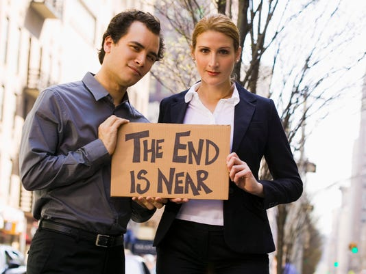 Couple holding The end is near sign