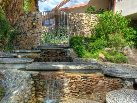 A walkway made of pebble-tech stepping stones crosses a stream on its way to the house's entry gates.