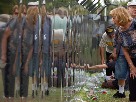 Arleen Soldano of Marco Island looks at names on the Traveling Vietnam Memorial Wall.