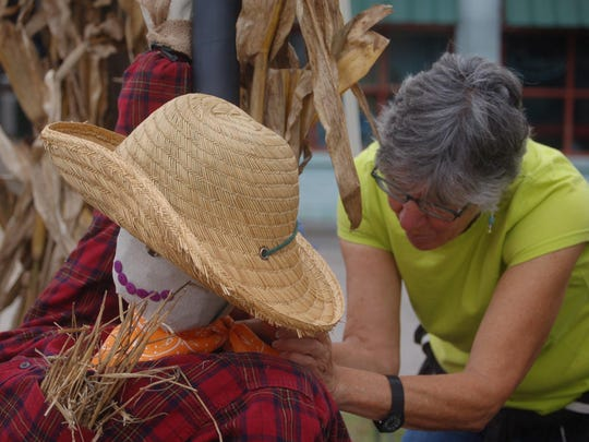 Mary Werner tucks a kerchief around a scarecrow's neck.