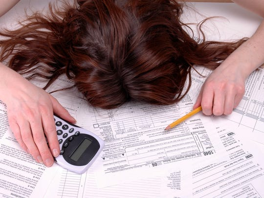 Woman collapsed over tax forms.