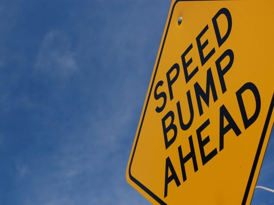 """A sign that says """"speed bump ahead."""""""
