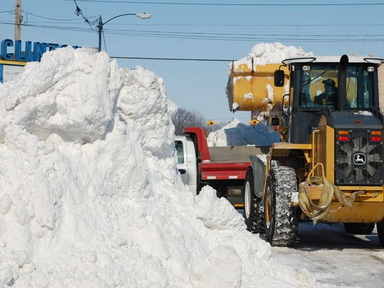 A city employee uses a front loader to load snow onto a small dump truck in March at Madison and Third streets.
