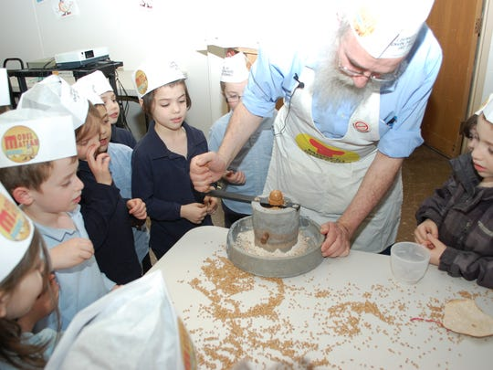 Rabbi Nechemiah Vogel, director of Chabad Lubavitch of Rochester, grinds wheat kernels while kids look on.