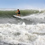 Surfers enjoy the high surf and swells from hurricane Joaquin Sunday afternoon at the Cocoa Beach Pier .