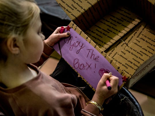 Local youths decorate boxes that were filled with toiletries,