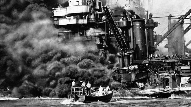 In this Dec. 7, 1941, photo provided by the Navy, a Navy launch pulls up to the blazing USS West Virginia to rescue a sailor during the attack on Pearl Harbor.