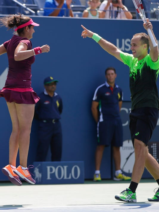 Sania Mirza, left, and Bruno Soares reacts after defeating Abigail Spears and Santiago Gonzalez in the mixed doubles final of the 2014 U.S. Open tennis tournament, Friday, Sept. 5, 2014, in New York. (AP Photo/Darron Cummings)