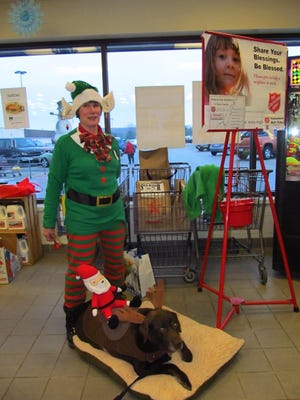 Laura Sutherland dressed as an elf at PicNSave along with her dog Jaxson Brown.