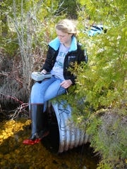 Ida Whitney using a device to measure the amount of dissolved oxygen in the stream water near Baileys Harbor in 2011.