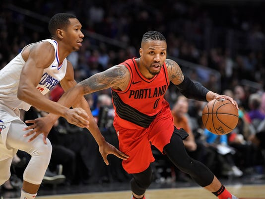 FILE - In this Tuesday, Jan. 30, 2018 file photo, Portland Trail Blazers guard Damian Lillard, right, dribbles past Los Angeles Clippers forward Wesley Johnson during the second half of an NBA basketball game in Los Angeles. The Trail Blazers have been known for their post-All-Star break revivals for the past two seasons. Those late-season rallies will no doubt be an ongoing theme in the congested Western Conference playoff race once Portland resumes the season on Friday, Feb. 23,2018 in Utah.  (AP Photo/Mark J. Terrill, File)