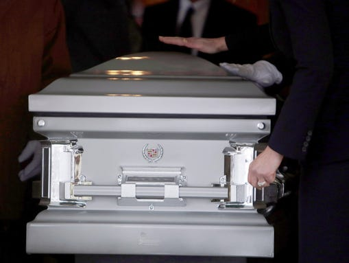 Cadillac emblems adorn the casket of Lee Randall, who