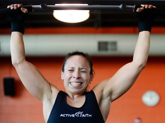 Angela Diaz finishes a set of pull-ups at the York JCC in York Township Thursday, October 20, 2016. Diaz was never into sports or competition. But after learning she had an autoimmune disease that could destroy her mobility, she fought back in an extreme way, training for a body building competition.